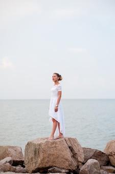 Молодая девушка на скалах в море