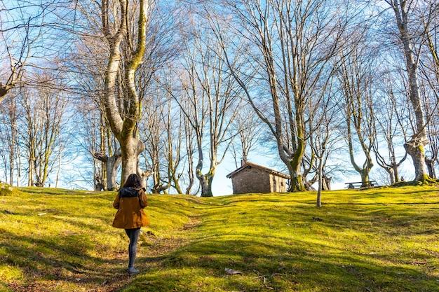 ギプスコアのオイアルツンの町にある、オイアンレクブナの森のトレッキングトレイルと背景の避難所にいる少女。バスク。スペイン