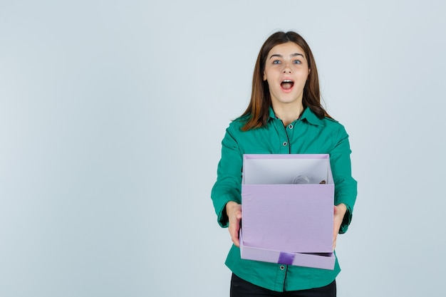 Young girl opening gift box, keeping mouth wide open in green blouse, black pants and looking surprised. front view.