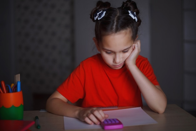 A young girl in an orange t-shirt is studying sitting at a desk. counts the numbers on the calculator.