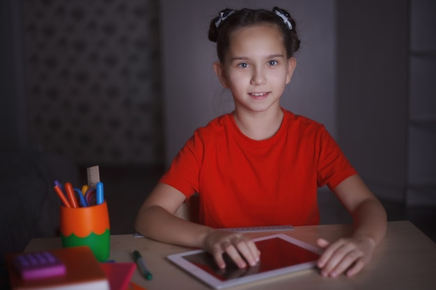 A young girl in an orange t-shirt is studying sitting at a desk. works on a tablet.