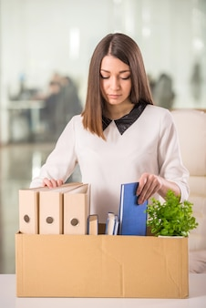 Young girl packing boxes in office.