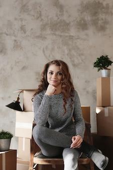 Молодая девушка собирает вещи для переезда в новую квартиру