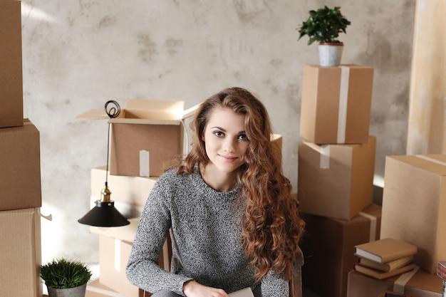 Молодая девушка собирает вещи, чтобы переехать в новое место