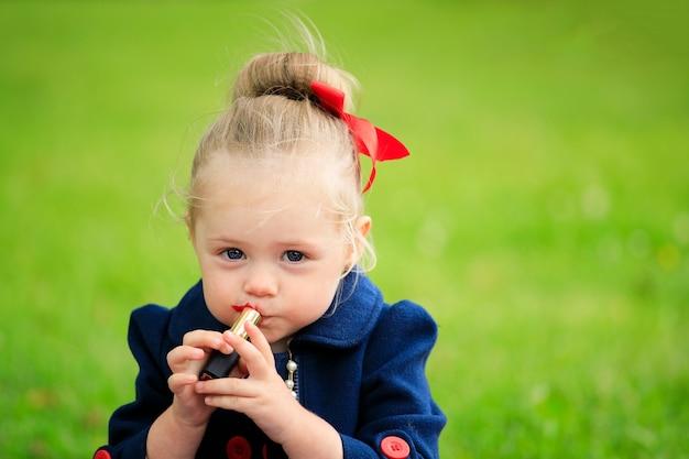 若い女の子は口紅で彼女の唇をペイントします