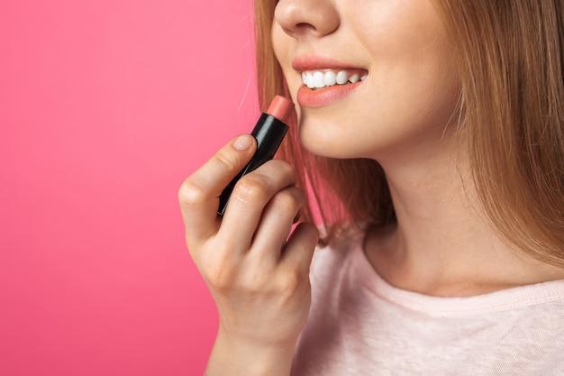 Молодая девушка красит губы помадой и смотрит в зеркало, на розовой стене, изолированные