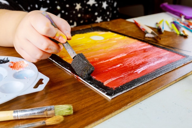 A young girl paints sunset on canvas with oil paint..