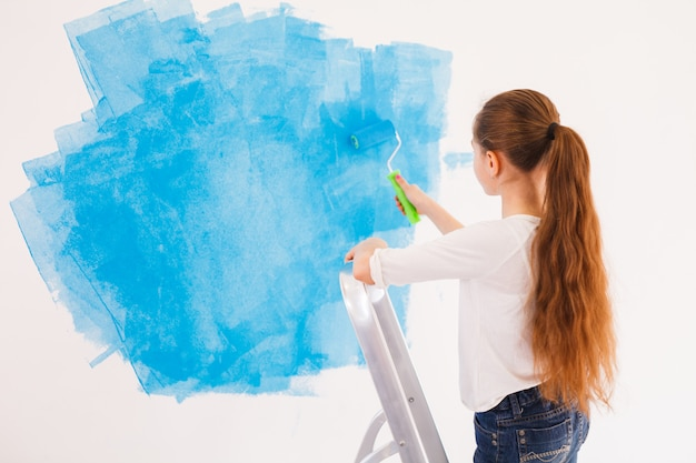 Young girl paints wall