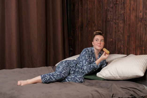 A young girl in pajamas lies on the bed and eats an eclair. happy weekend at the hotel. enjoyment of idleness.