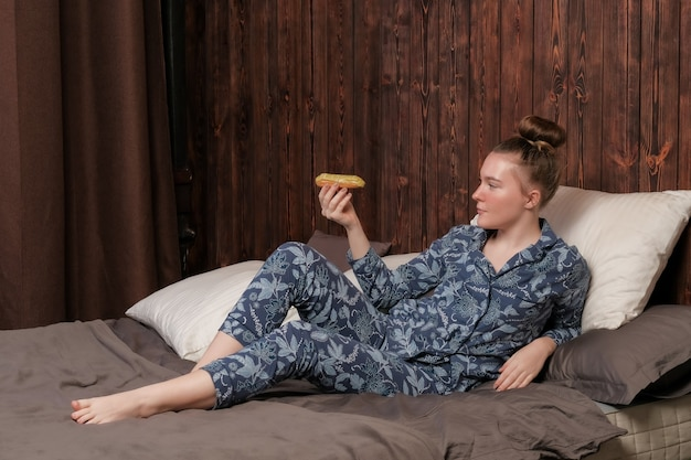 A young girl in pajamas sits on the bed and eats an eclair.
