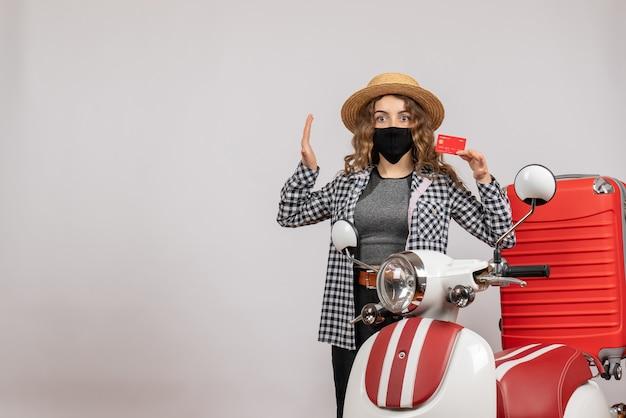 Giovane ragazza in cappello panama che tiene la carta in piedi vicino al motorino rosso red