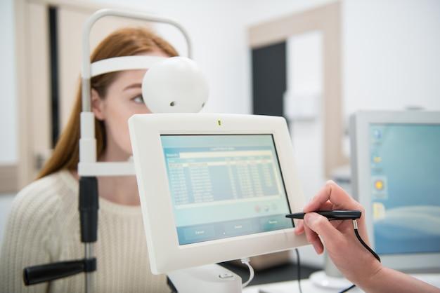 医師の眼科医でレセプションの若い女の子の患者診断眼科機器