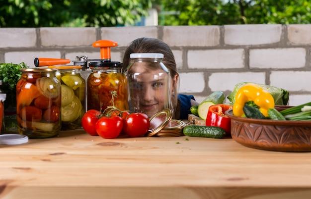 空のガラスの瓶をのぞき、カメラで微笑んで、新鮮な野菜とジャムの瓶で覆われた木製のテーブルで庭の屋外で若い女の子