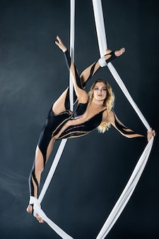 A young girl performs the acrobatic elements in the aerial silk