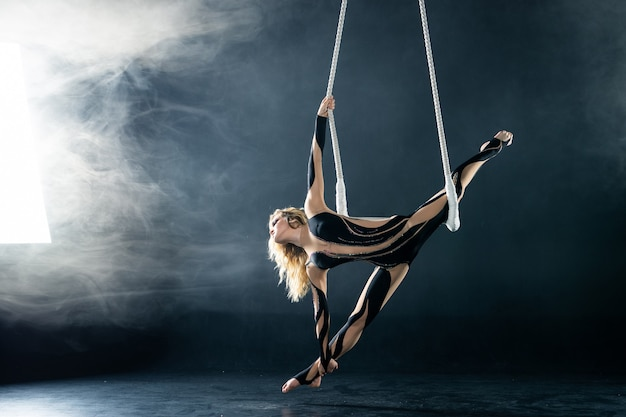 A young girl performs the acrobatic elements in the air trapeze