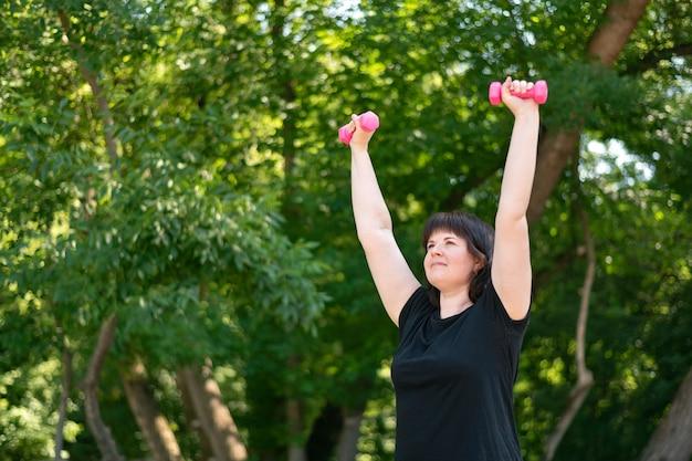 어린 소녀는 아령의 도움으로 손을 위한 운동을 합니다. 야외 운동. 공원에서의 피트니스, 건강한 생활 방식