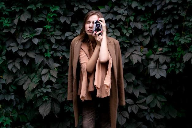 Молодая девушка фотограф с пленочной камерой