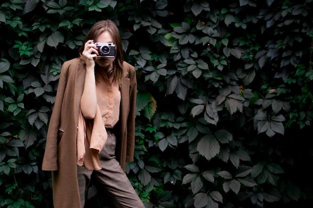 Молодая девушка-фотограф стоит с пленочной камерой возле стены из листьев в лесу, женщина фотографирует на природе
