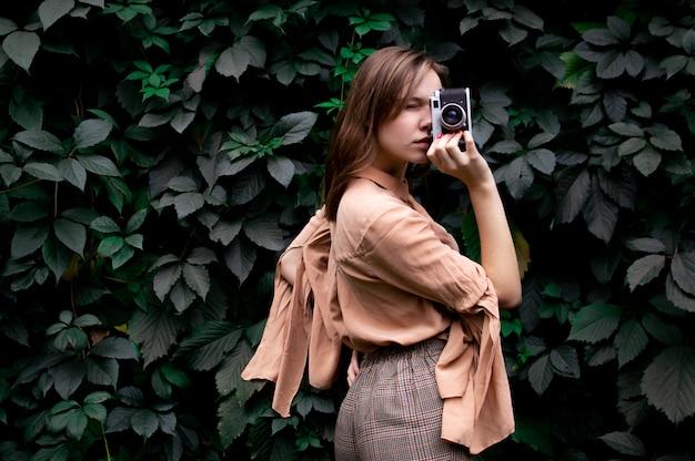 Молодая девушка фотограф стоит с пленочной камерой возле стены листьев в лесу