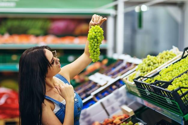 若い女の子はスーパーマーケットでブドウを選ぶ