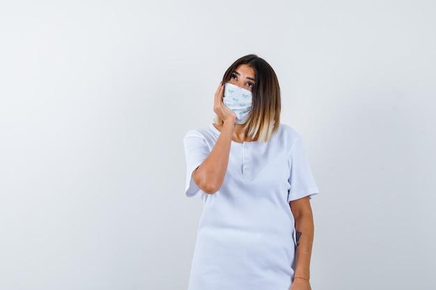 Молодая девушка под рукой в белой футболке, маске и задумчиво смотрит, вид спереди.