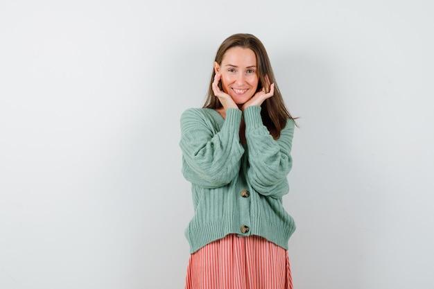 ニットウェア、スカート、幸せそうに見える手に顔を枕で若い女の子。正面図。
