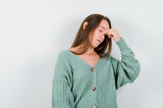 若い女の子は、ニットウェアで鼻の橋をつまんで、疲れ果てているように見えます。正面図。