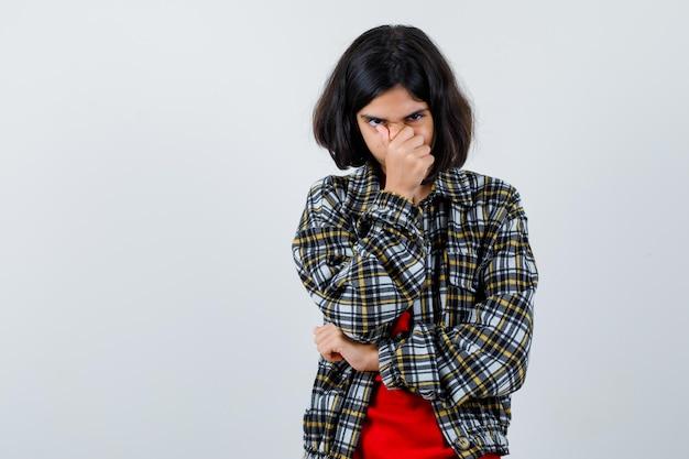 어린 소녀는 체크 셔츠와 빨간 티셔츠에서 악취가 나서 코를 꼬집고 해리처럼 보입니다. 전면보기.