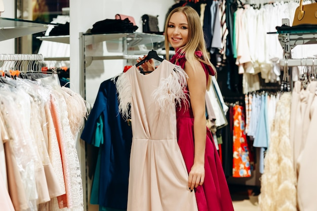 Young girl in pink in the store presents a beautiful, new dress