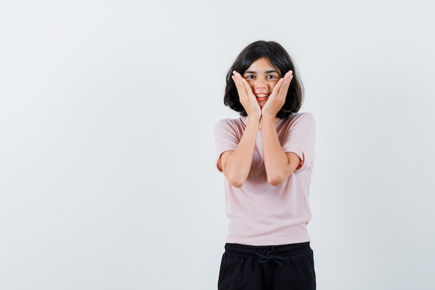 Young girl in pink t-shirt and black pants holding hands on cheeks and looking cute