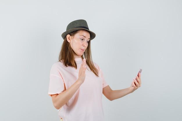 Giovane ragazza in maglietta rosa, cappello agitando la mano in chat video e guardando allegra, vista frontale.