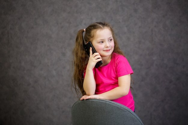 A young girl in a pink t-shirt talks on the phone