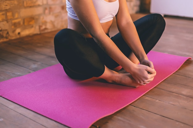 Young girl on a pink yoga mat is sitting in the lotus position alone holding her feet