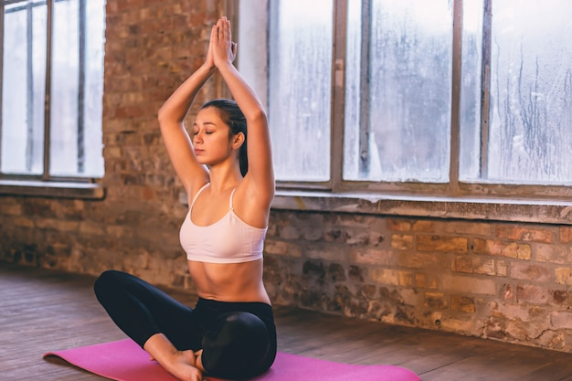 Young girl on a pink yoga mat sits in a lotus position alone with her hands up