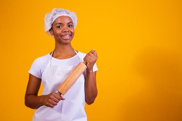Создатель пиццы маленькой девочки на желтой предпосылке держа скалку.