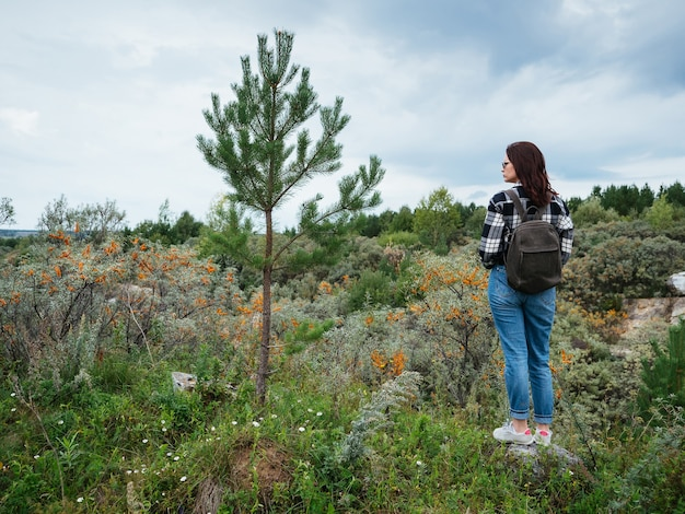 A young girl in a plaid shirt, blue jeans, with a leather backpack, and dark hair stands in the mountains, copyspace