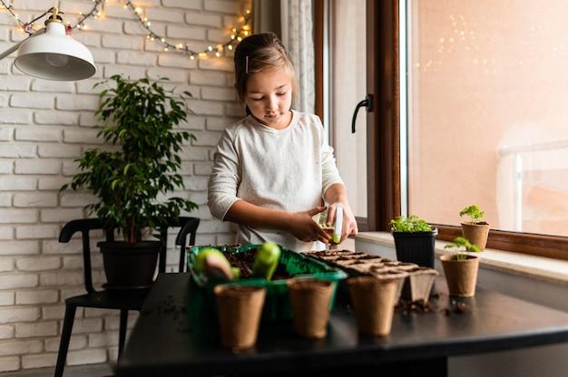 Молодая девушка сажает урожай дома