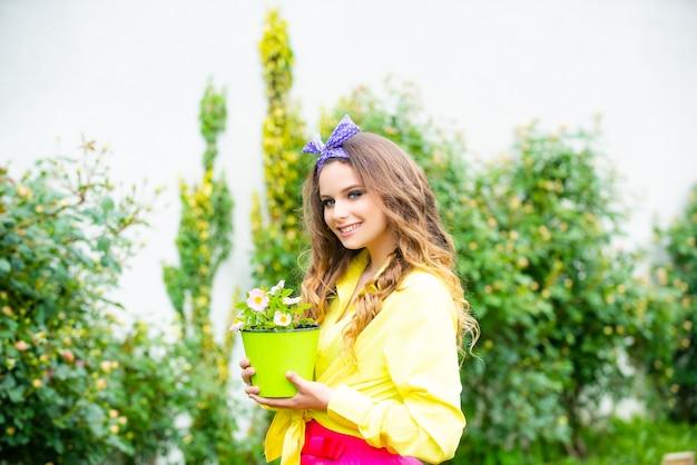 鉢植えの花に花を植える少女