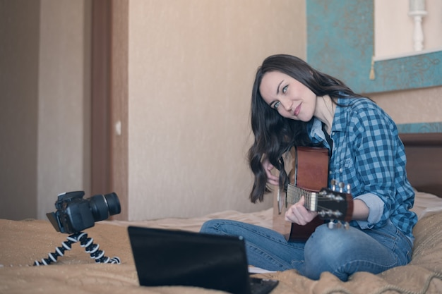 Young girl playing acoustic guitar in the room