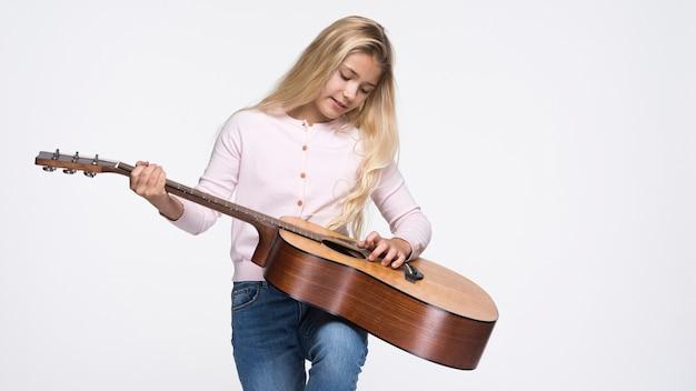 Молодая девушка играет на гитаре