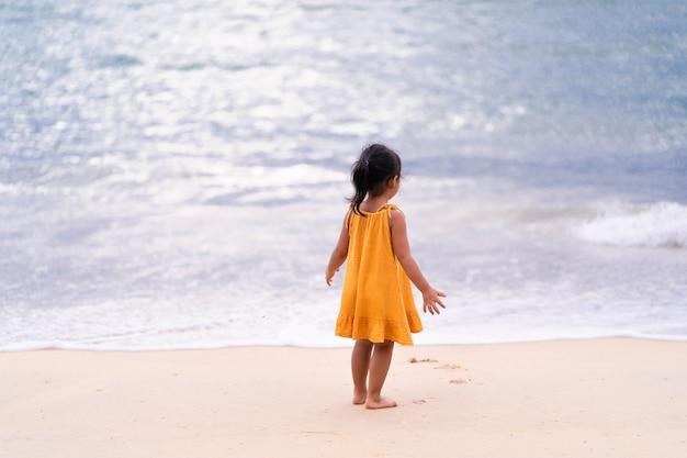 황혼에서 바다 해안에서 재생하는 어린 소녀.