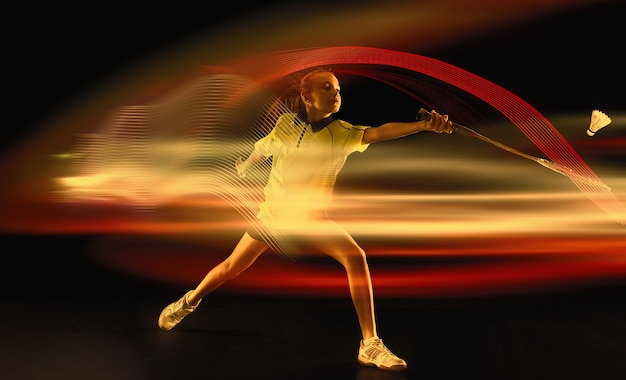 Молодая девушка играет в бадминтон на темном студийном фоне спортсменка в действии с неоновым светом