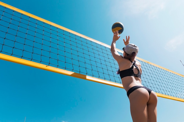 Young girl playing beach volleyball. beach volleyball championship. the woman reaches for the ball. throwing a yellow volleyball over the net. victory point. outdoor sports games.