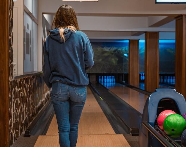 Молодая девушка играет в боулинг