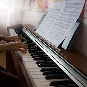 Маленькая девочка играет на цифровом пианино. вид сбоку.
