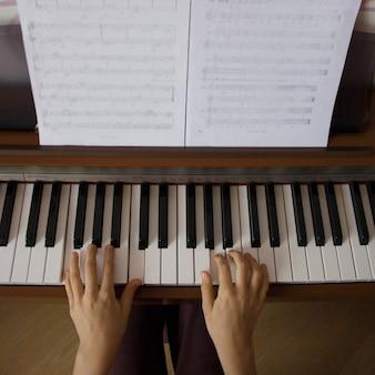 Маленькая девочка играет на цифровом пианино. вид сверху