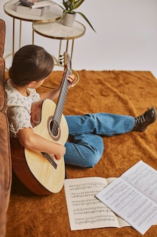 집에서 기타를 연주하는 어린 소녀