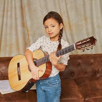 Молодая девушка играет на гитаре дома