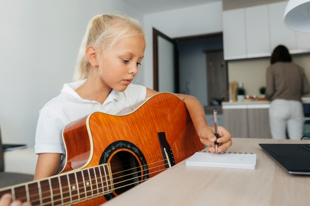 Young girl playing a guitar at home