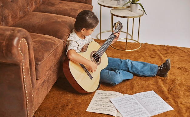 Young girl playing guitar at home
